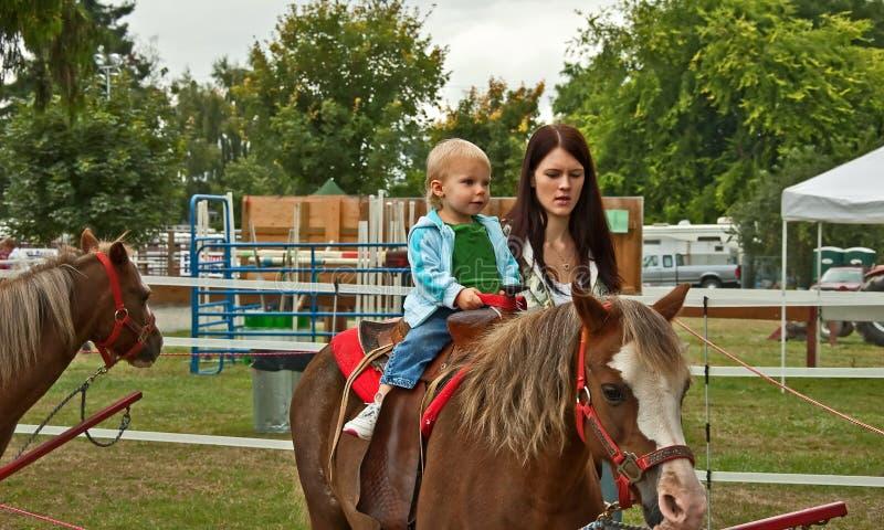 Litet barnflicka med mamman först Pony Ride royaltyfria foton