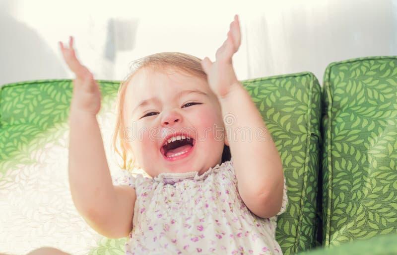 Litet barnflicka som ler och applåderar henne händer royaltyfri foto