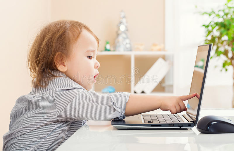 Litet barnflicka som pekar till hennes bärbar datordatorskärm arkivfoto