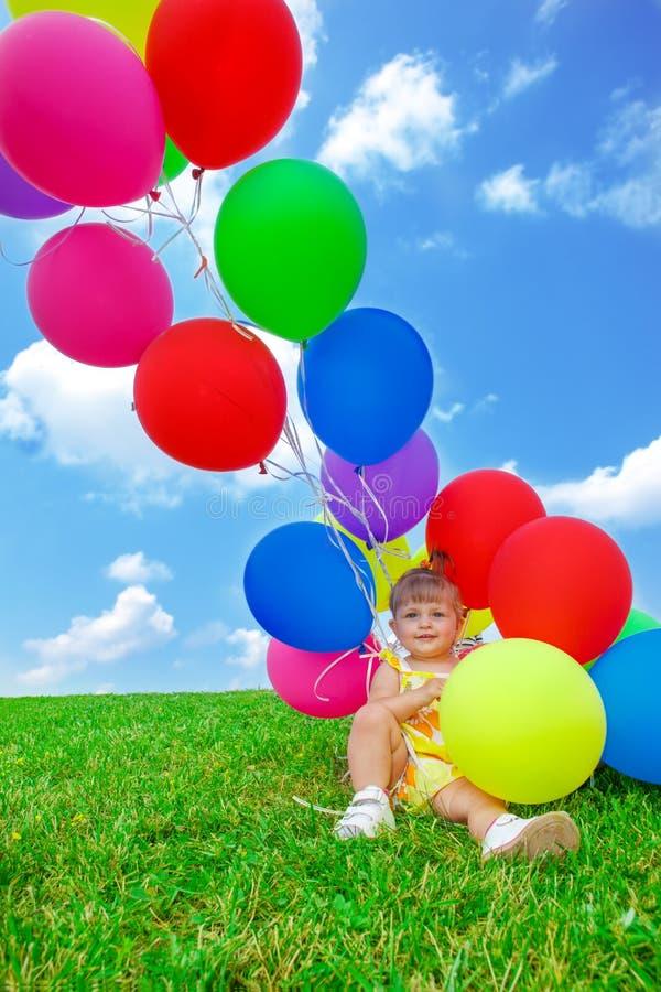 Litet barnflicka som sitter en grupp av ballonger royaltyfria foton