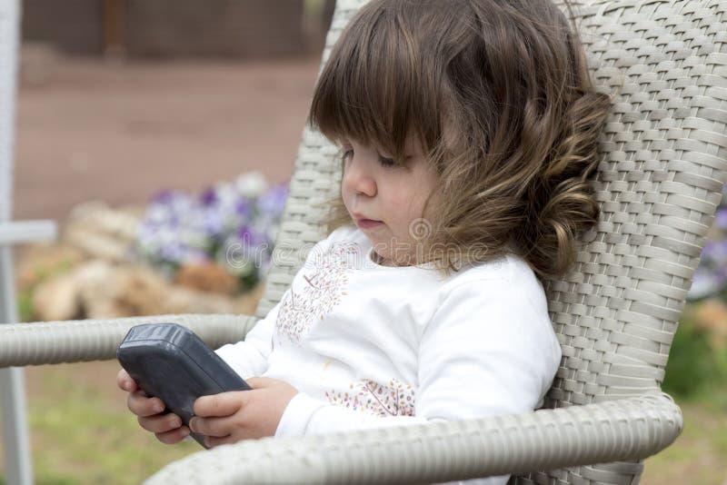 Litet barnflicka som spelar med telefonen royaltyfria bilder