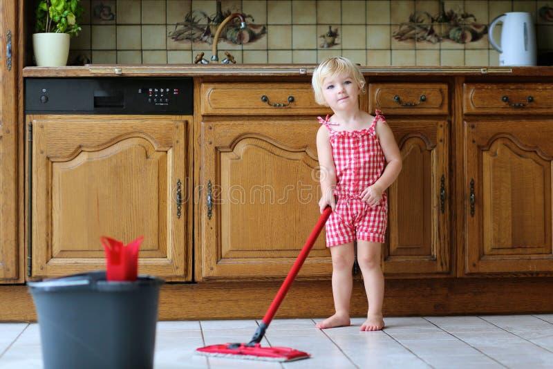 Litet barnflicka som spelar moppa inomhus kökgolvet royaltyfri fotografi