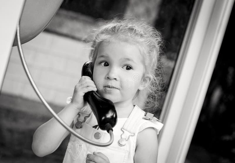 Litet barnflicka som talar vid stadstelefonen arkivbilder