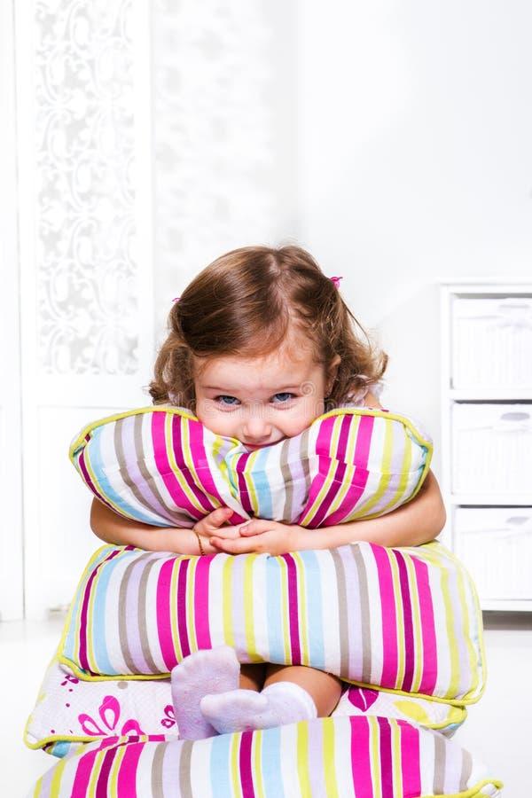 Litet barnflickan med kudder arkivfoto