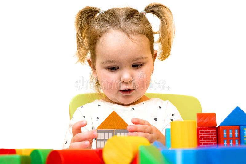 Litet barnflickan spelar med färgrika träkvarter över vit bakgrund Lilla barnet bygger ett hus ut ur kvarter royaltyfri bild