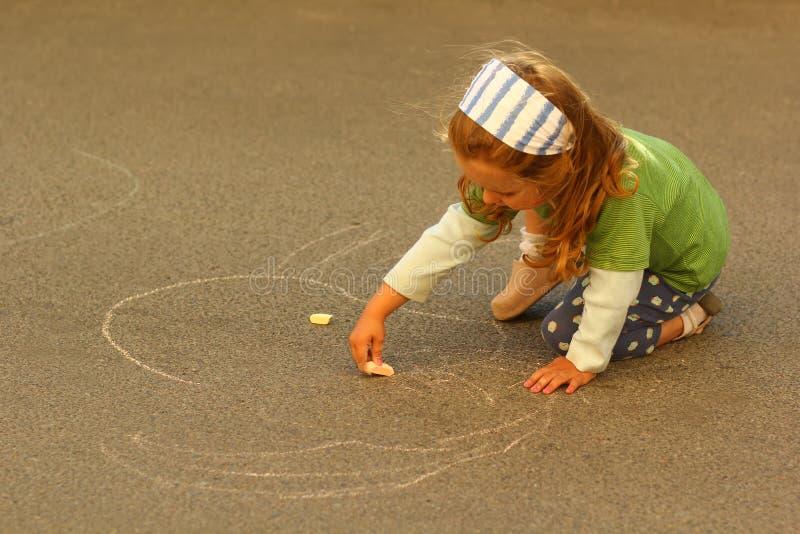 Litet barnflickateckning med krita på asfalt fotografering för bildbyråer