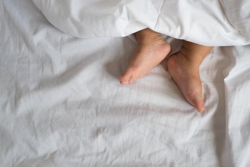 Litet barnfot i det vita säng, arket och kudden arkivbild