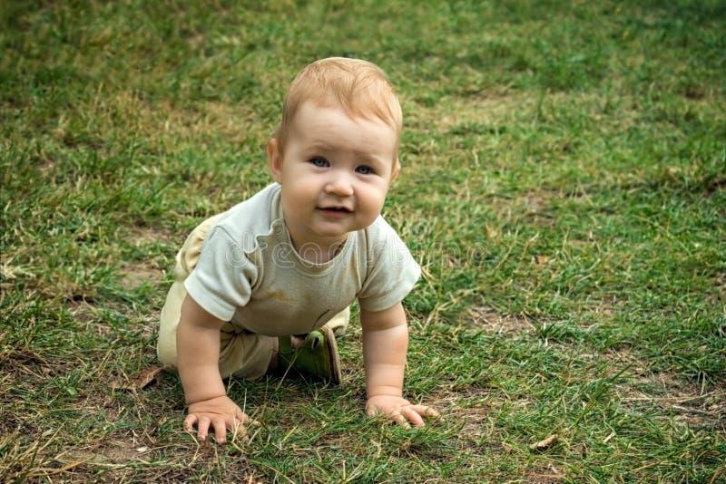 Litet barnleenden och flyttningar på alla fours runt om gården i den öppna luften royaltyfri fotografi