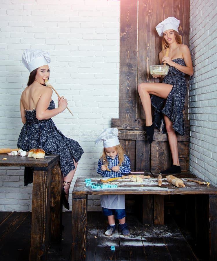Litet barnpojke och flickor i kockhattar i kök royaltyfri foto