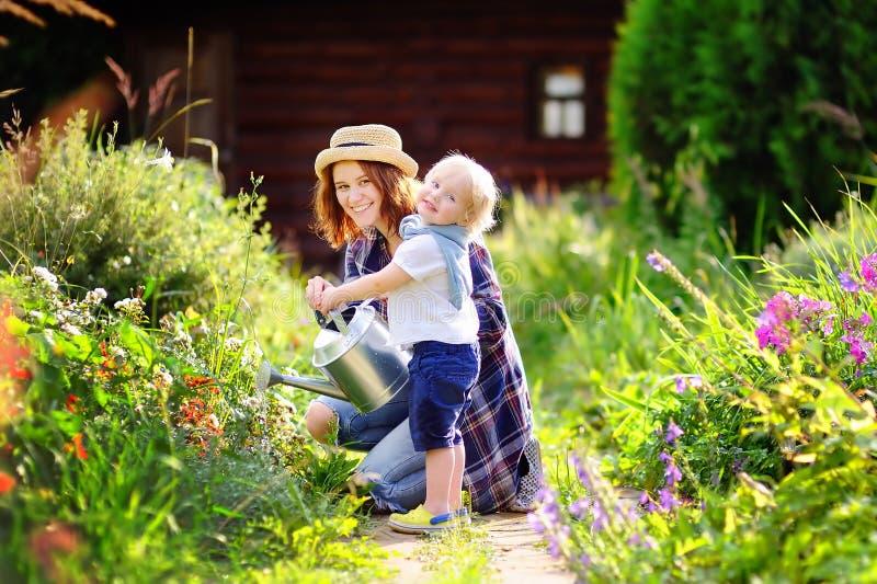 Litet barnpojke och hans moder som bevattnar växter i trädgården arkivbild