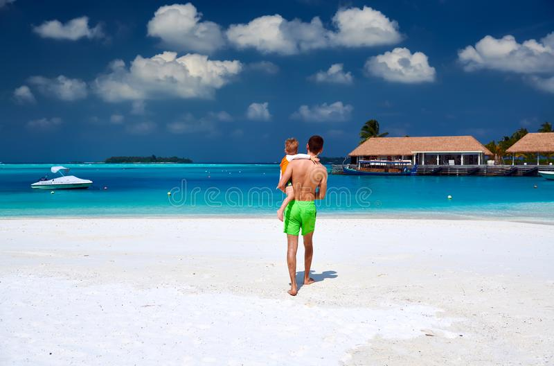 Litet barnpojke på stranden med fadern arkivbild