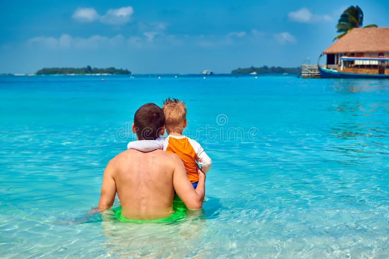 Litet barnpojke på stranden med fadern royaltyfri bild