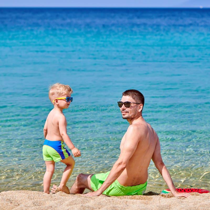 Litet barnpojke på stranden med fadern royaltyfri foto