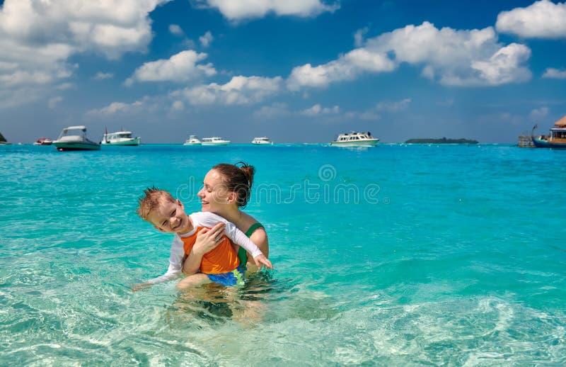 Litet barnpojke på stranden med modern arkivbilder