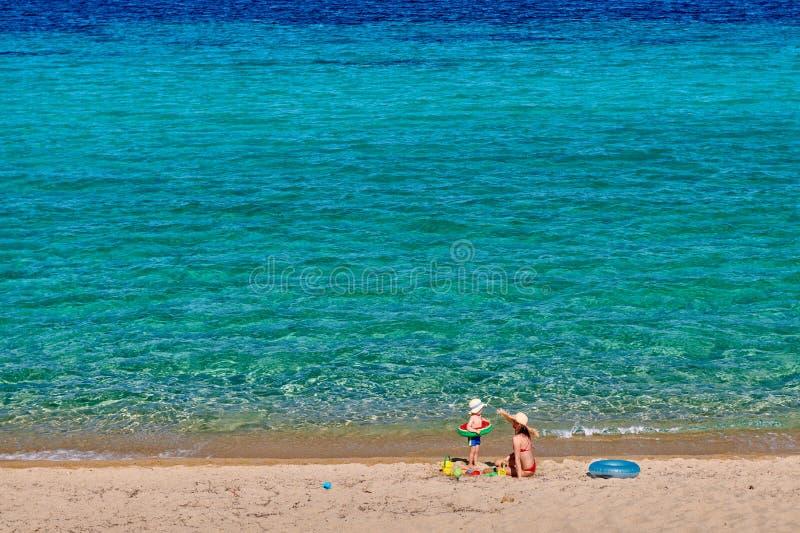 Litet barnpojke på stranden med modern arkivbild