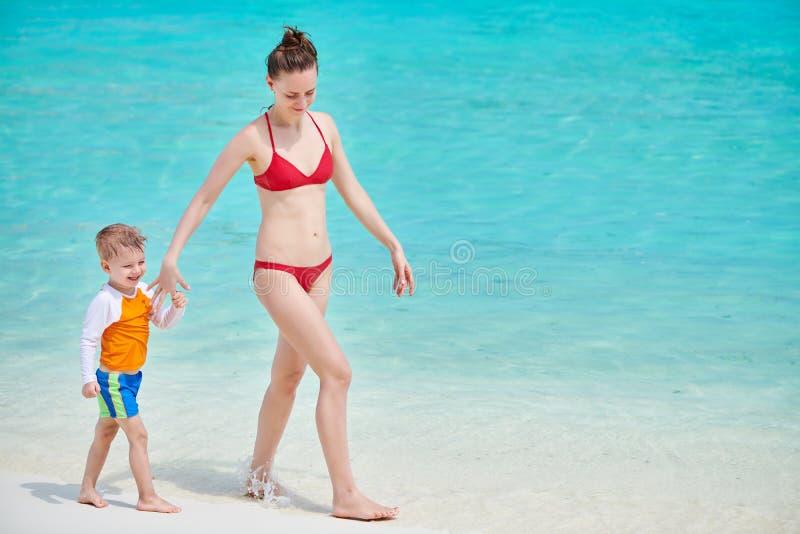 Litet barnpojke p? stranden med modern royaltyfria bilder