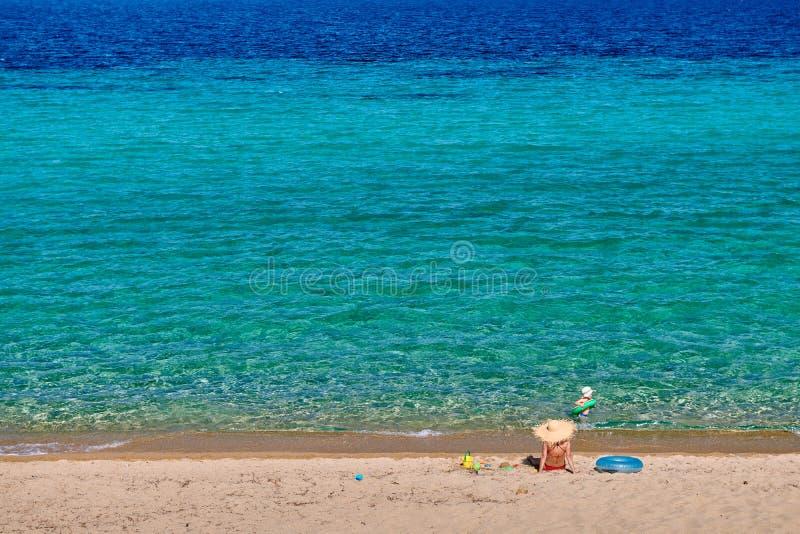 Litet barnpojke p? stranden med modern arkivbild