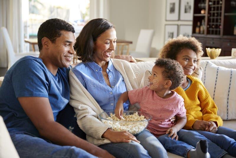 Litet barnpojke som äter popcorn som sitter på soffan med hans syster och föräldrar i deras vardagsrum som tillsammans håller ögo royaltyfria bilder