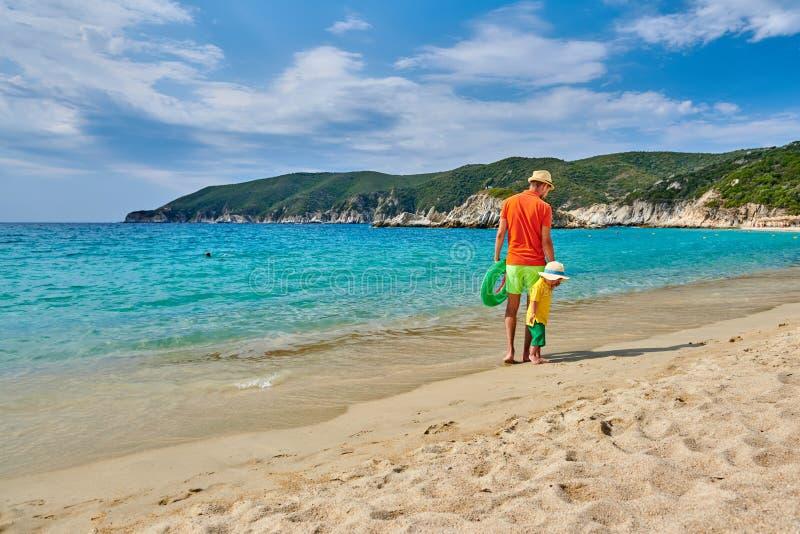 Litet barnpojke som går på stranden med fadern arkivfoto