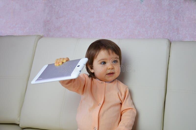 Litet barnpojke som hemma spelar med den digitala minnestavlan på soffan arkivfoto