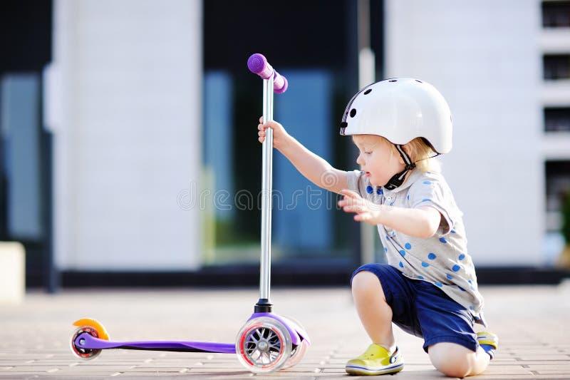 Litet barnpojke som lär att rida sparkcykeln arkivbilder