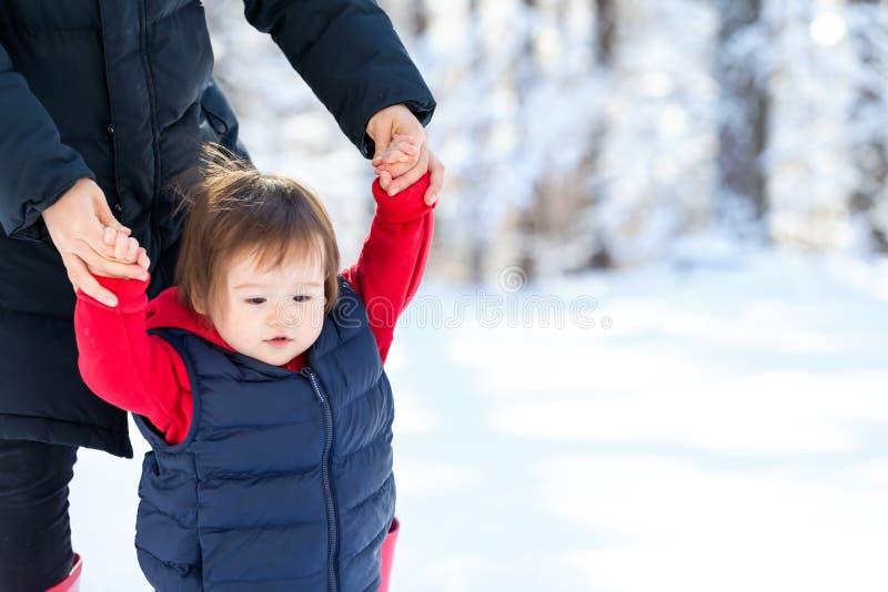 Litet barnpojke som spelar i snön fotografering för bildbyråer
