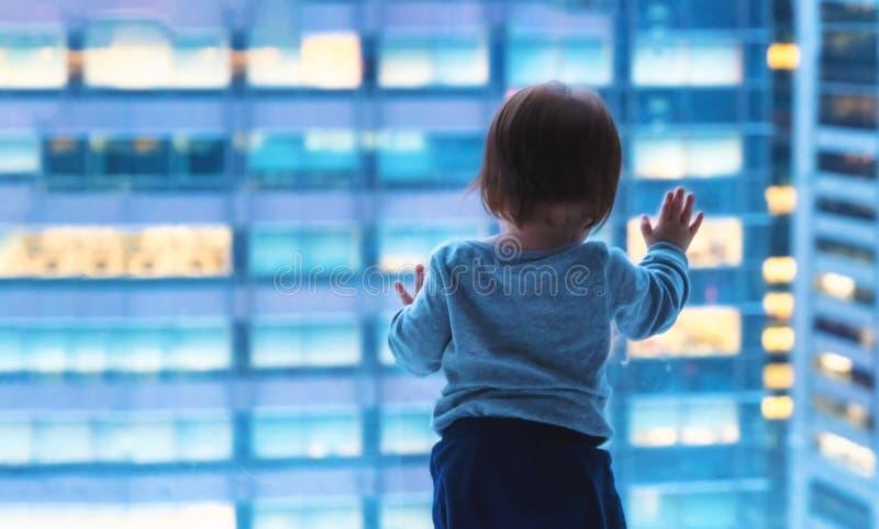Litet barnpojke som ut ser fönstret i Tokyo royaltyfri foto