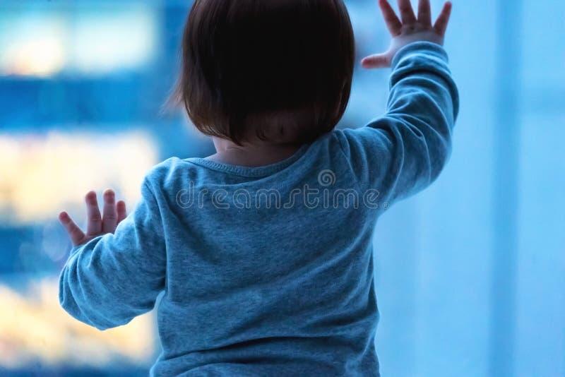 Litet barnpojke som ut ser fönstret i Tokyo royaltyfri bild