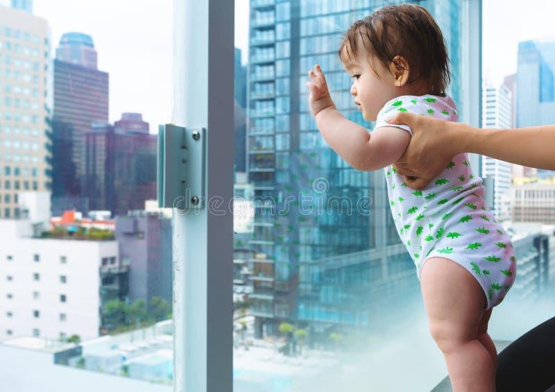 Litet barnpojke som ut ser på staden en glass balkong royaltyfria foton