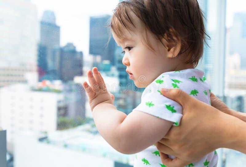 Litet barnpojke som ut ser på staden en glass balkong arkivfoton