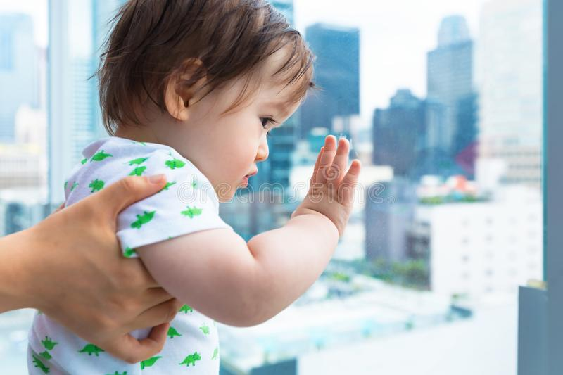 Litet barnpojke som ut ser på staden en glass balkong royaltyfri fotografi