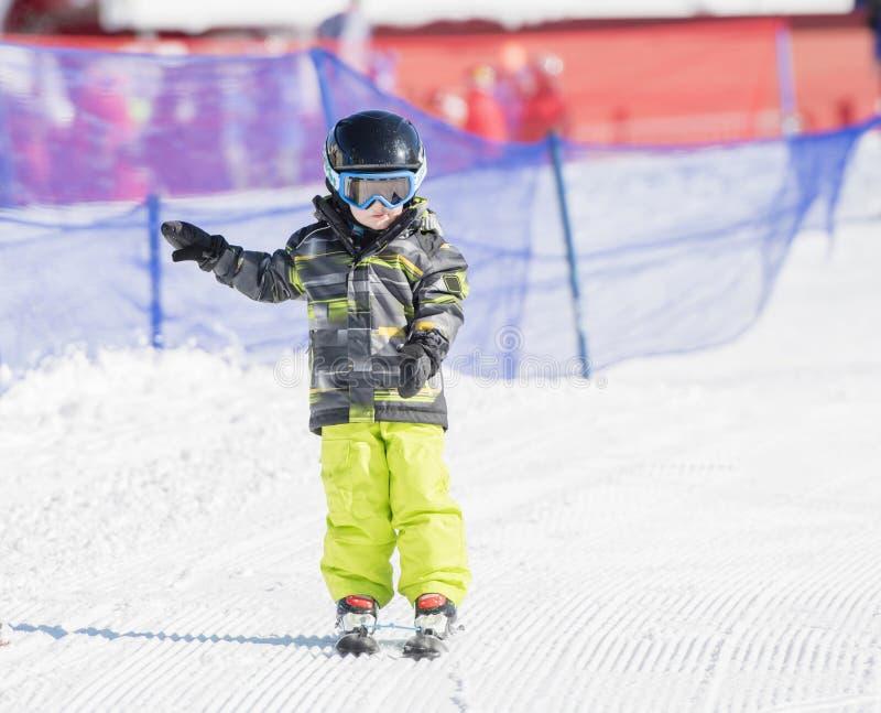 Litet barnpojke som varmt & i kläs bra skida för säkerhetskugghjul som är sluttande arkivfoton