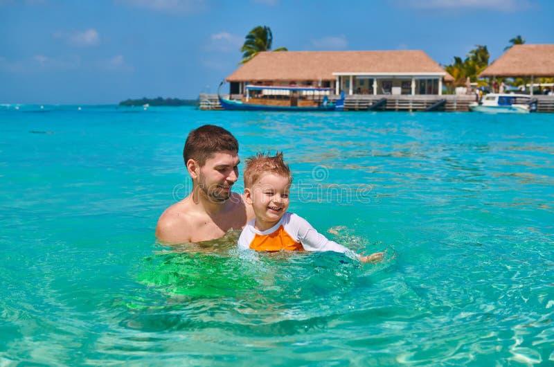 Litet barnpojken l?r att simma med fadern arkivfoton