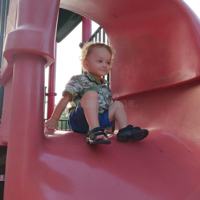 Litet barnpojken sätta sig upptill av en hal glidbana royaltyfri fotografi
