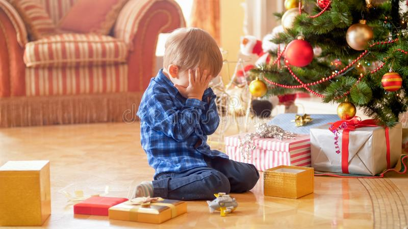 Litet litet barnpojkesammanträde under julgranen och gråt arkivfoto
