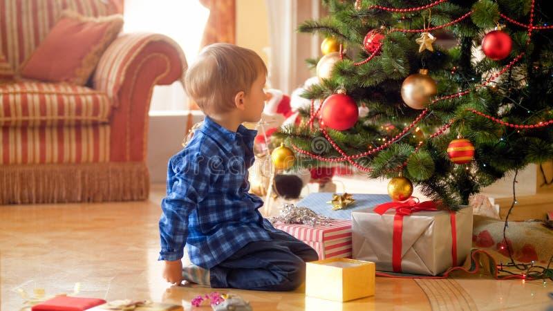 Litet litet barnpojkesammanträde under julgranen och se på stor bunt av julklappar fotografering för bildbyråer