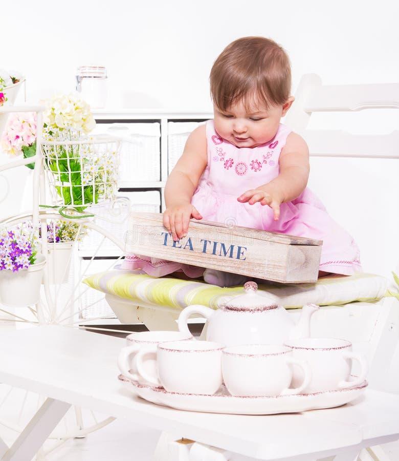 Litet barn som leker med teauppsättningen arkivfoto