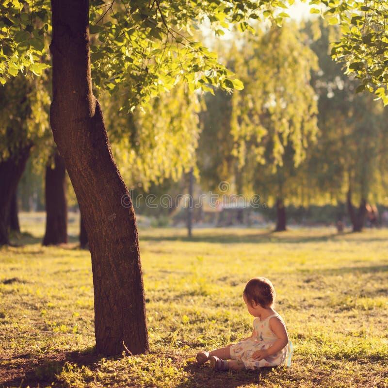 Litet barnsammanträde under trädet arkivfoto