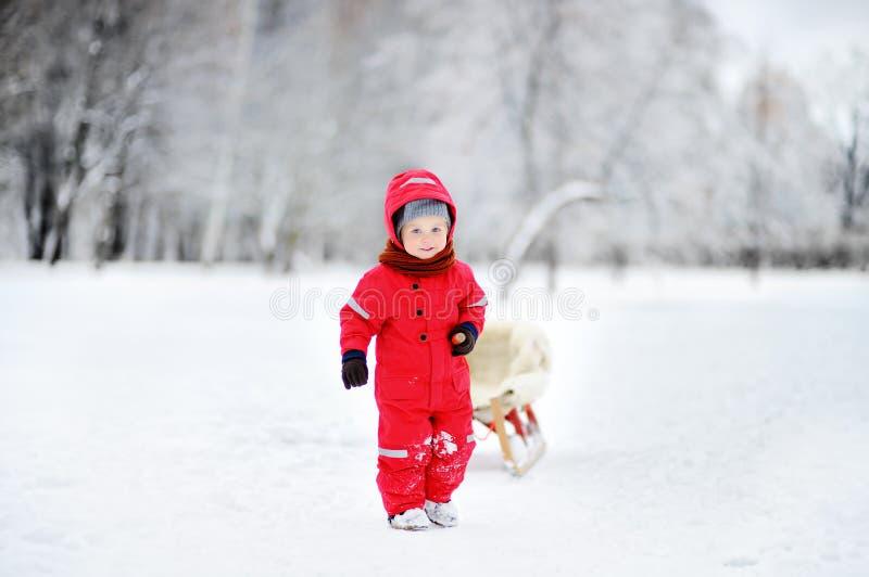 Litet barnunge som rider en pulka Barnlek utomhus i snö royaltyfri foto