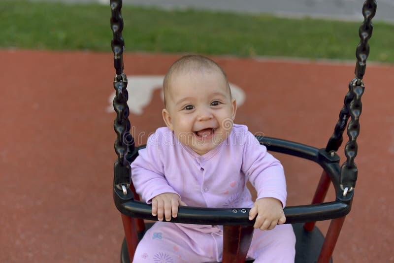 Litet behandla som ett barn att sitta på en gunga i parkerar och leenden lyckligt royaltyfria bilder