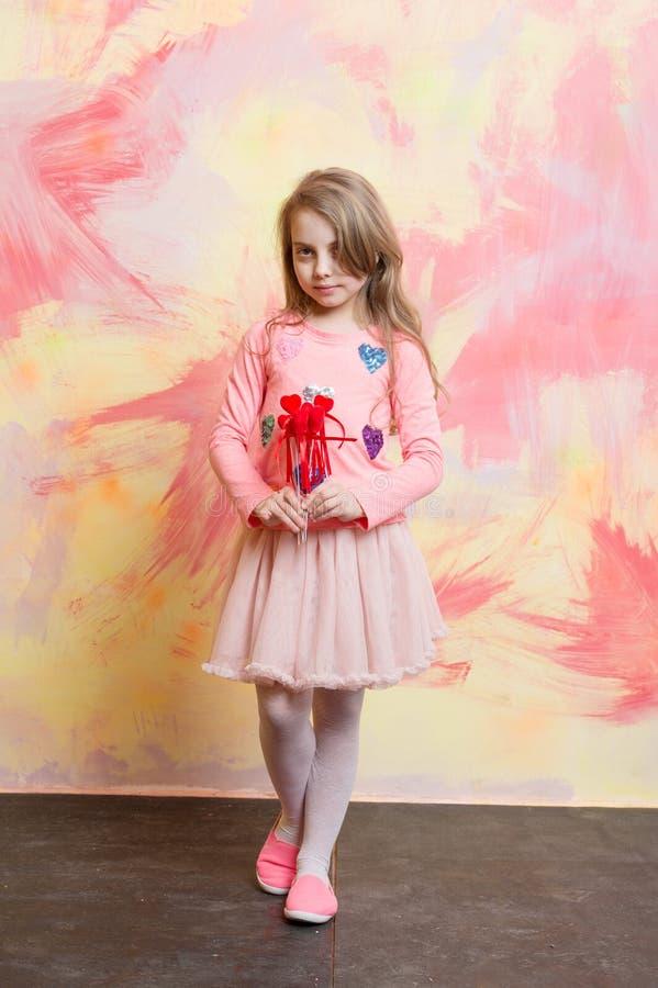 Litet behandla som ett barn för valentindagen för flickan hållande dekorativa röda hjärtor arkivbilder