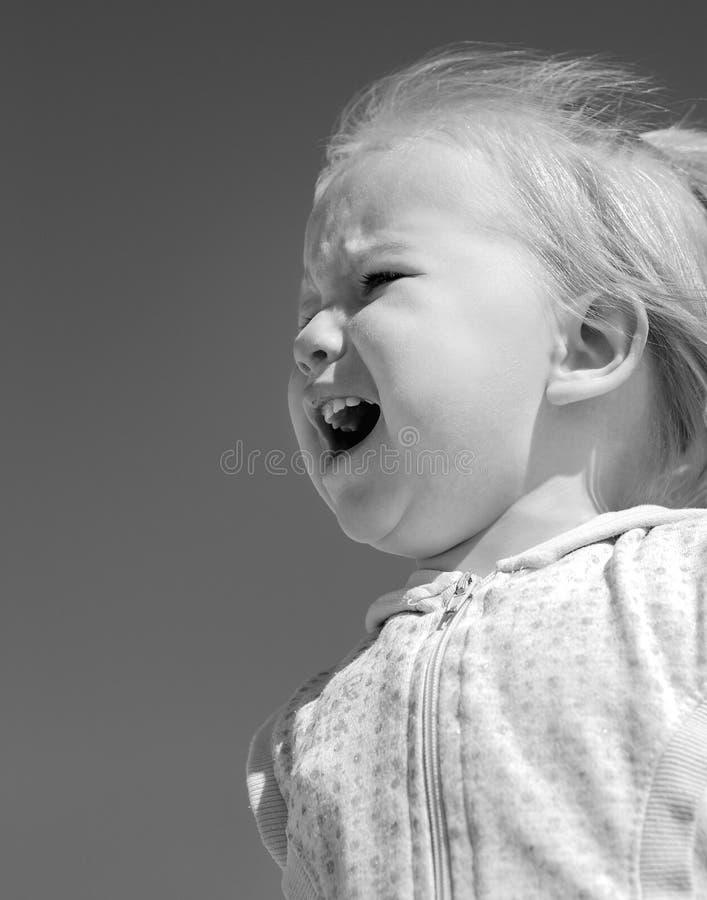 Litet behandla som ett barn flickan som gråter på bakgrunden av blå himmel royaltyfria foton