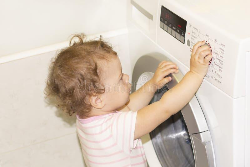 Litet behandla som ett barn flickan trycker på knappar på tvättmaskinen royaltyfri bild