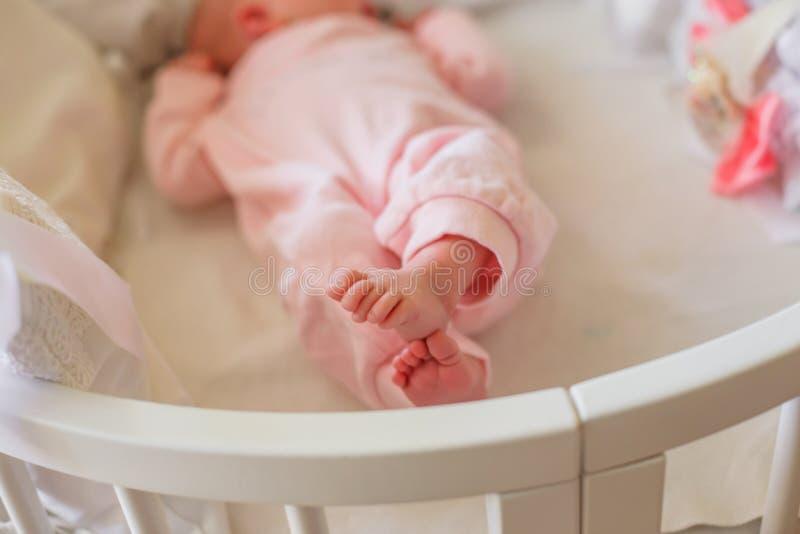 Litet behandla som ett barn klädd fot i rosa romper Mycket små fingrar av det nyfött Barnet har korsat ben och lögner i en rund v arkivbilder
