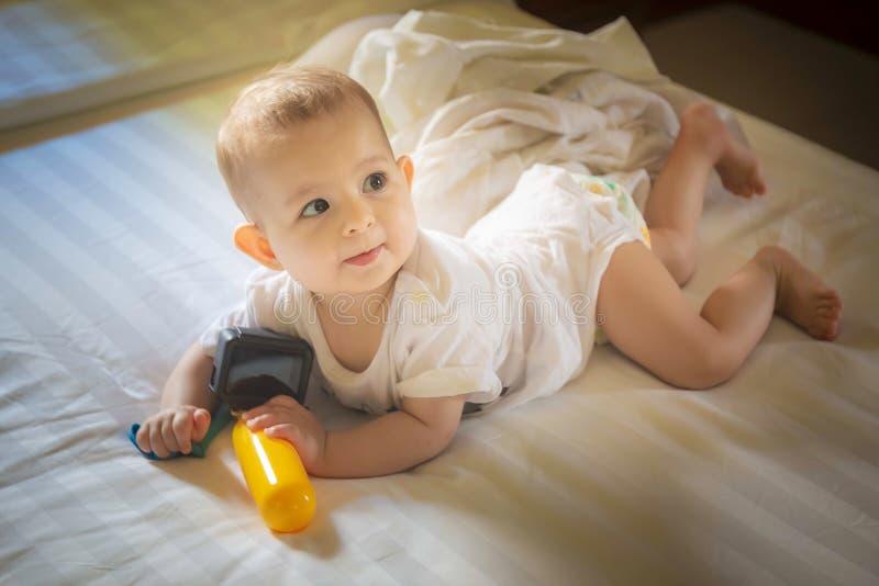 Litet behandla som ett barn 8 månader lögner på en vit säng begynnande flickalekar med handlingkameran och se mamman royaltyfri fotografi