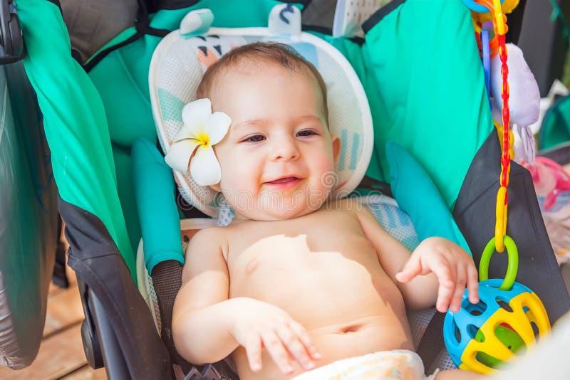 Litet behandla som ett barn på 8 gamla månader med en frangipaniblomma bak örat Sitter i en loppsittvagn och tycker om solen på e arkivfoto