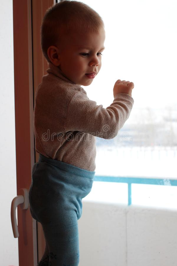 Litet behandla som ett barn pojken som klättras på en hög fönsterbräda som ut ser fönstret som ler fara arkivfoton