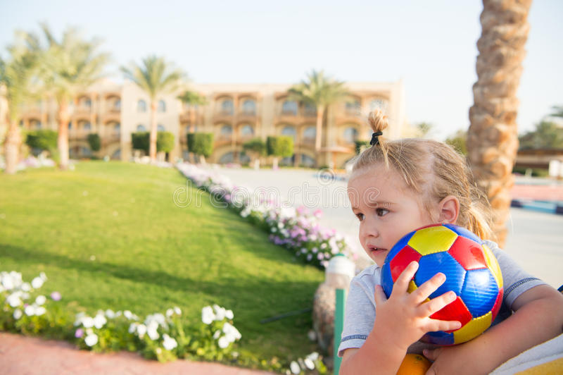 Litet behandla som ett barn pojken med färgrikt spela för boll som är utomhus- arkivbild