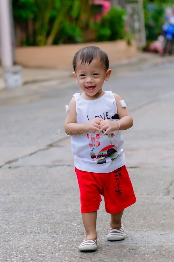 Litet behandla som ett barn pojken som promenerar gatan Behandla som ett barn promenera vägen Behandla som ett barn lilla barnet  royaltyfria bilder