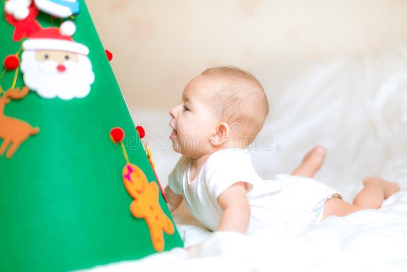 Litet behandla som ett barn spädbarnet Spela med en julgran ligga för underlag Surprisedly ser under xmas-trädet studerar en leks royaltyfria bilder